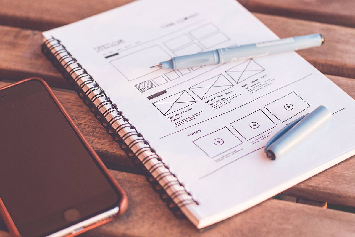 website wireframe sketched in a notepad