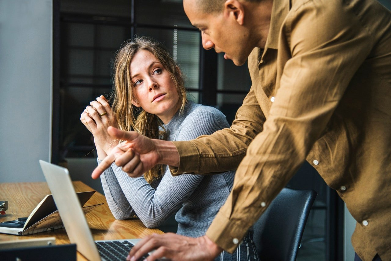 Agile Development: Man working with woman and pointing at a laptop screen